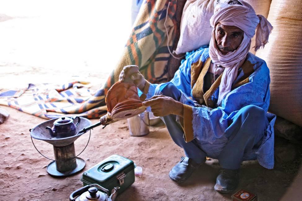 Nomade du désert du Sahara au Maroc, entrain de préparer le thé traditionnel