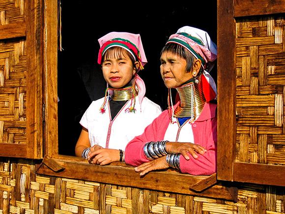 Femmes girafes birmanes à la fenêtre de leur maison