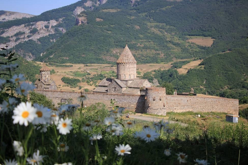 Monastère de Tatev dans un paysage de montagnes et de fleurs