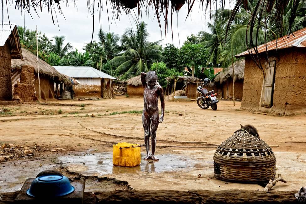 Un enfant qui se lave dans un village au Togo