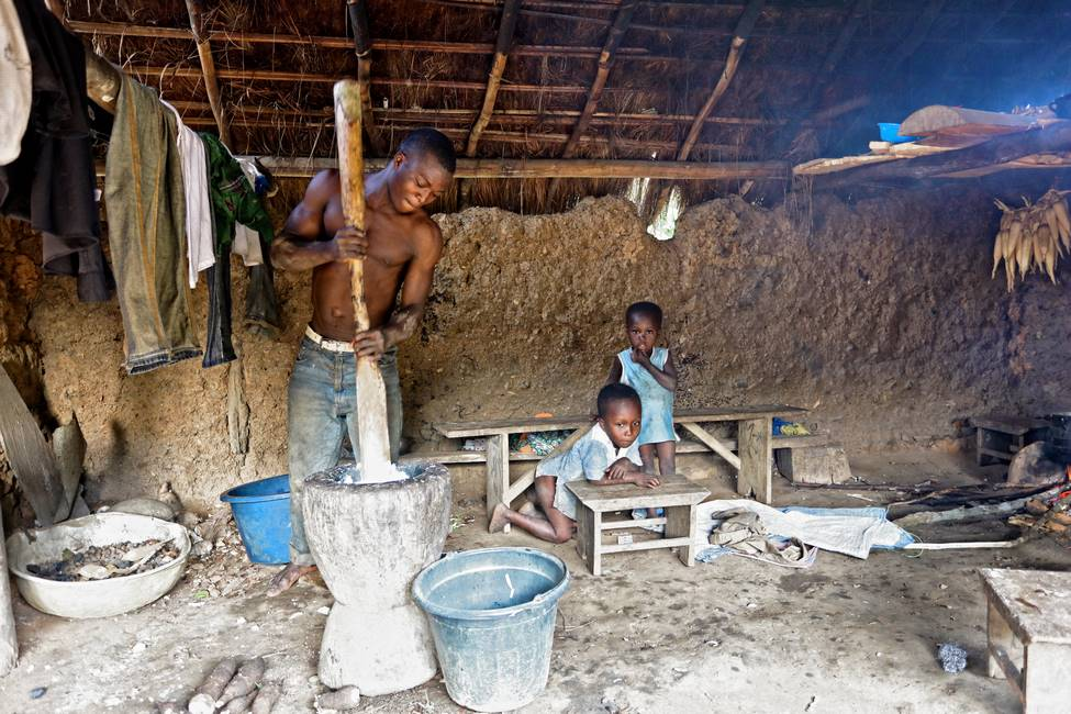 Homme qui prépare le foufou plat traditionnel au Togo