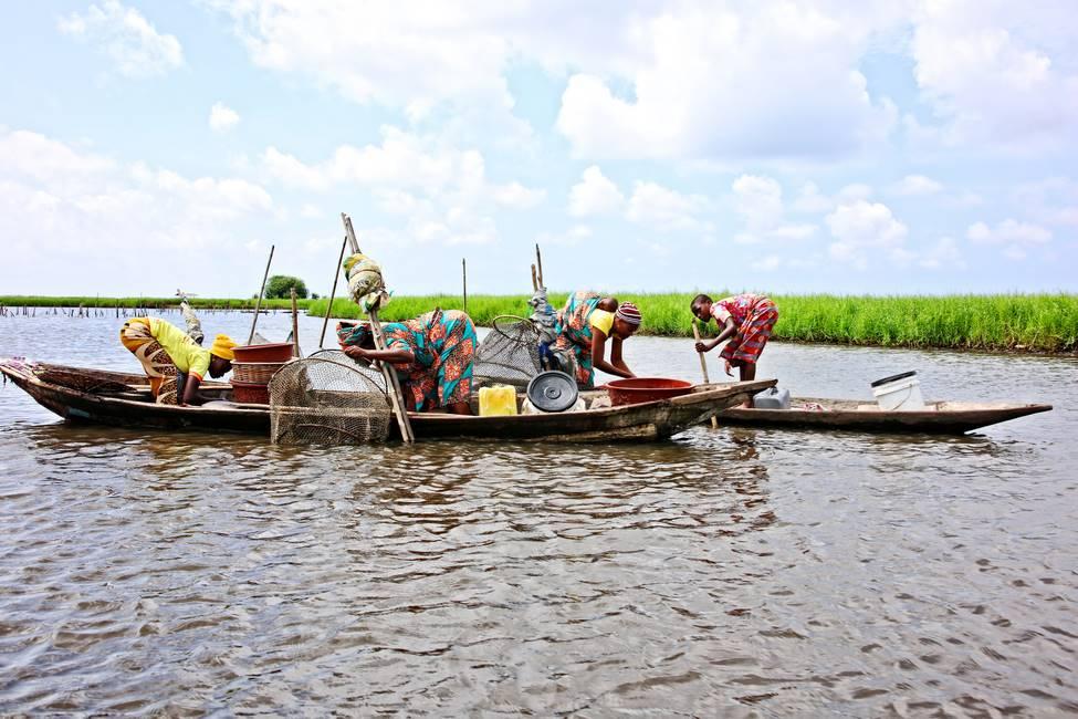 Femmes qui pêchent sur une pirogue dans la cité lacustre de Ganvié au Bénin