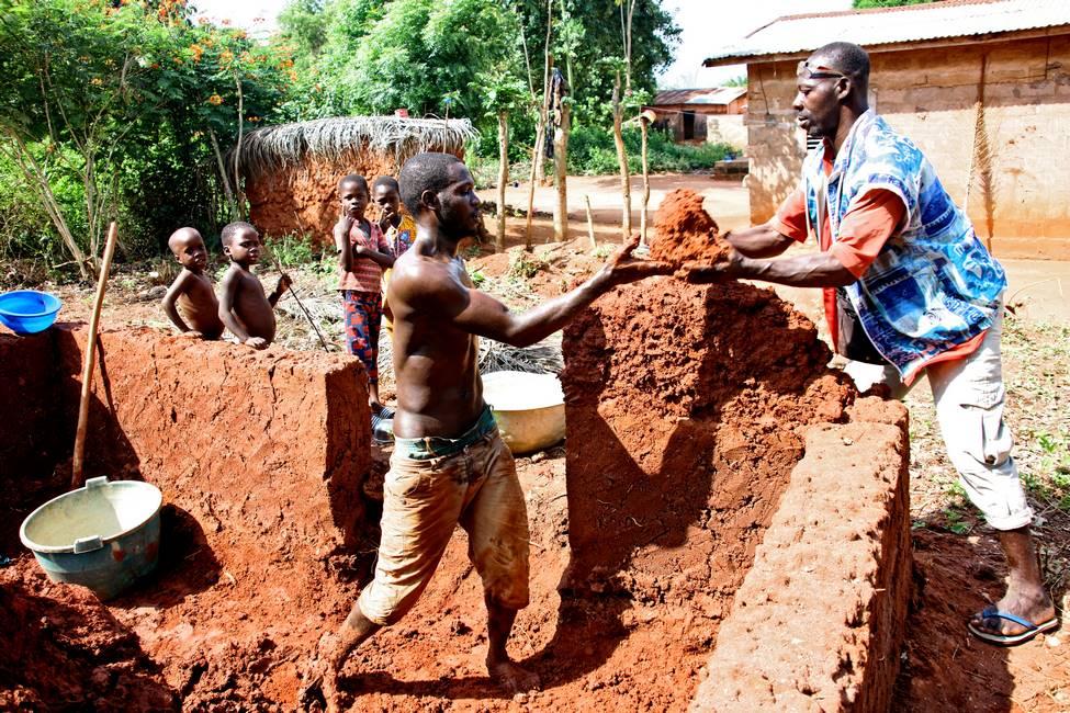 Hommes construisant une maison en terre banco au Bénin