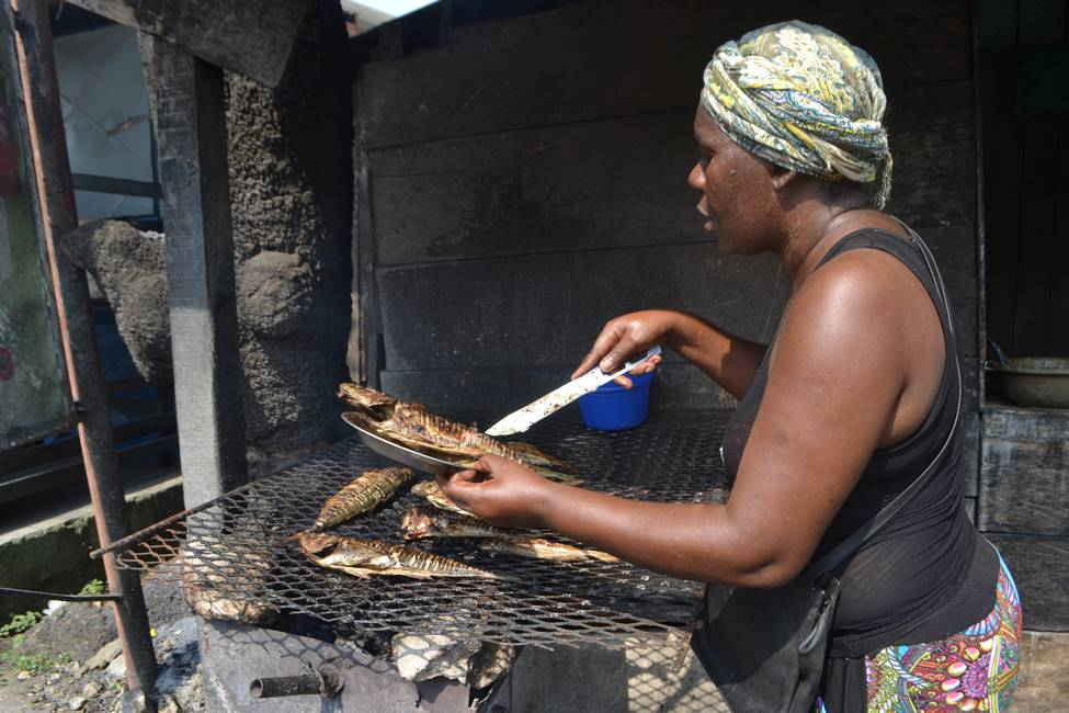 Braiseuse de poisson sur un marché au Cameroun