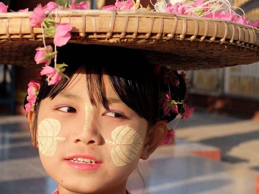 Jeunie fille au visage peint au thanaka vendant des fleurs en Birmanie