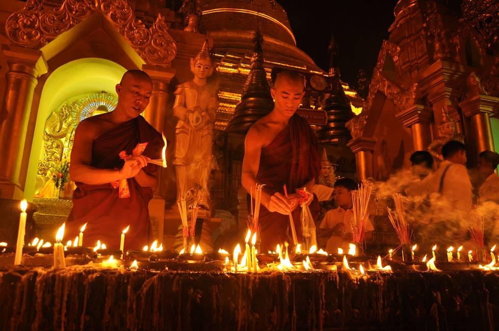 Moines bouddhistes allumant des bougies en offrande à Yangon en Birmanie