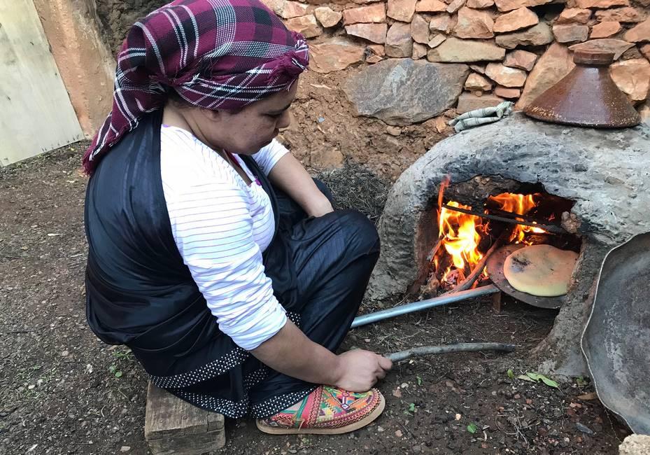 Berbère faisant cuire son pain dans un four traditionnel au Maroc