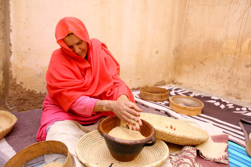 Femme fabricant la semoule de couscous à la main au Maroc