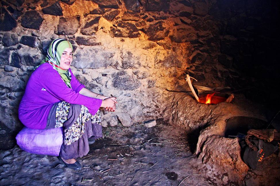 Femme berbère faisant cuire son pain dans un four en terre traditionnel au Maroc