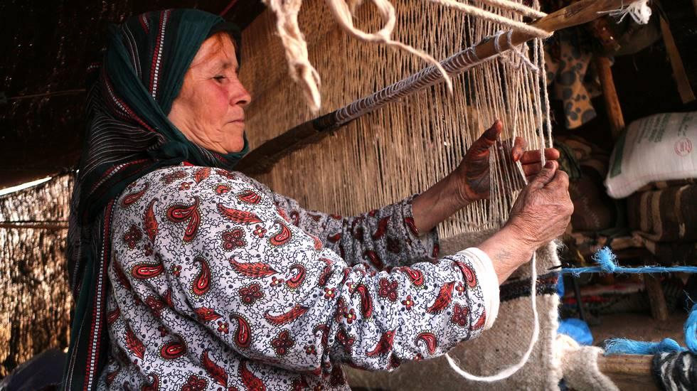 Nomade tissant un tapis avec la laine de ses moutons au Maroc
