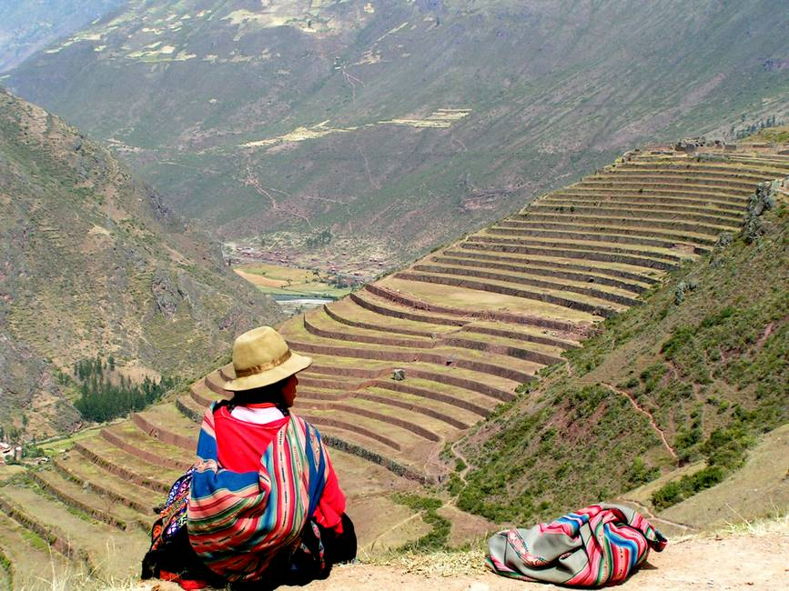 Péruvienne assise devant un panorama de cultures en terrasse