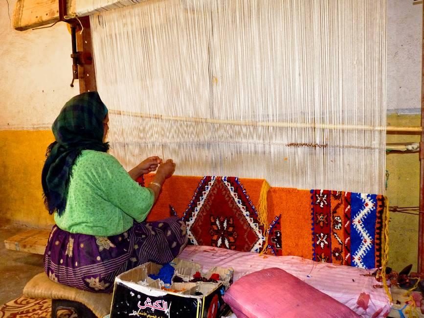 Femme berbère tissant un tapis en laine au Maroc