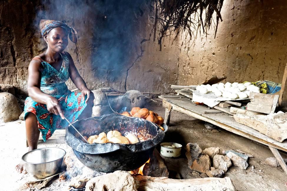 Togolaise faisnt cuire des petits pains au feu de bois